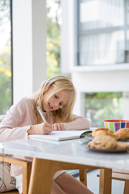 Cute blonde girl doing her homework at home by Jovo Jovanovic for Stocksy United