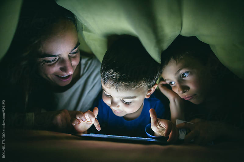 Mother and her sons watching a video under the bed sheets. by BONNINSTUDIO for Stocksy United