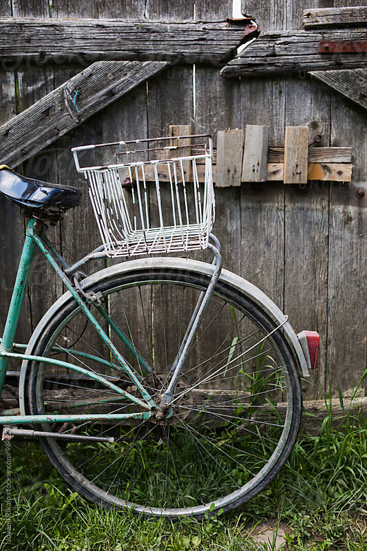 An old bicycle leaning against the wooden fence by Jovana Rikalo for Stocksy United