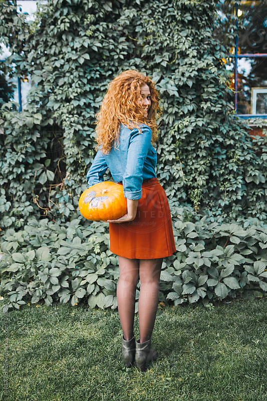 Red headed woman holding orange pumpkin by Danil Nevsky for Stocksy United