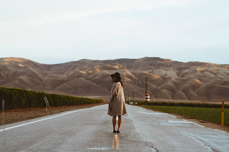 young woman standing in the road at sunset by Jesse Morrow for Stocksy United