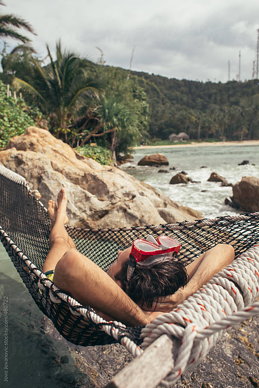 Young man wearing his snorkelling mask laying on a hammock on a cliff looking at the ocean and sky by Jovo Jovanovic for Stocksy United