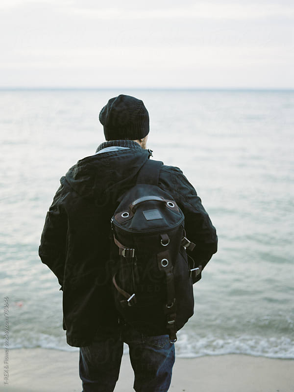 Man looking away with backpack while standing on sandy shore by Danil Nevsky for Stocksy United