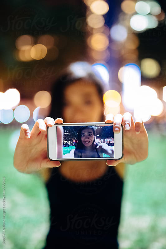 Woman holding a cell phone at the park at night by Good Vibrations Images for Stocksy United