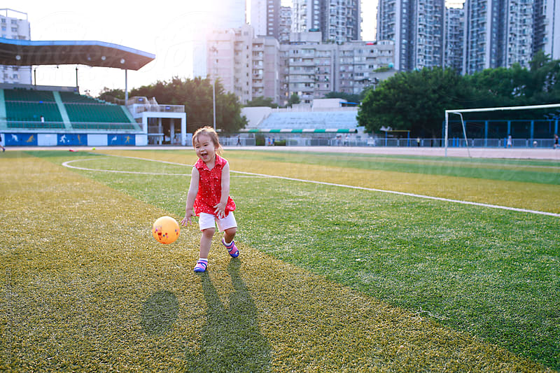 little asian girl playing with a ball on the football field by cuiyan Liu for Stocksy United