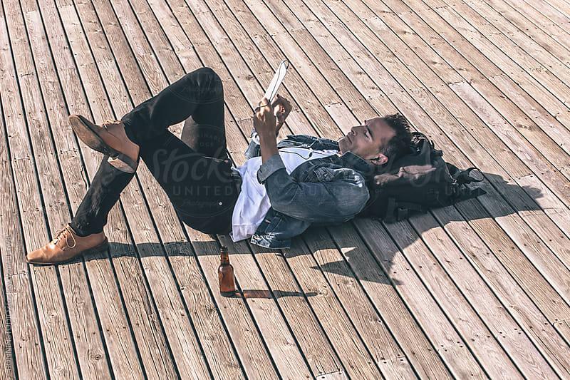Man resting drinking beer on wooden floor. by BONNINSTUDIO for Stocksy United