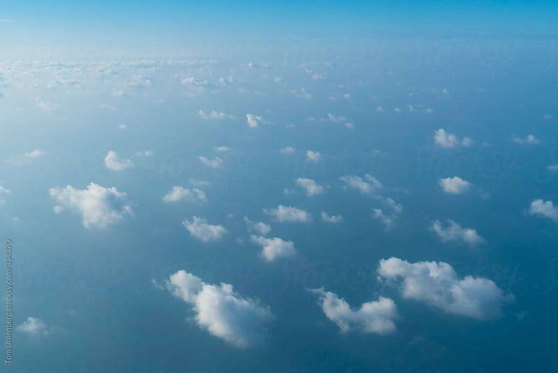 Flying above Small, Fluffy Clouds and a Blue Ocean by Tom Uhlenberg for Stocksy United