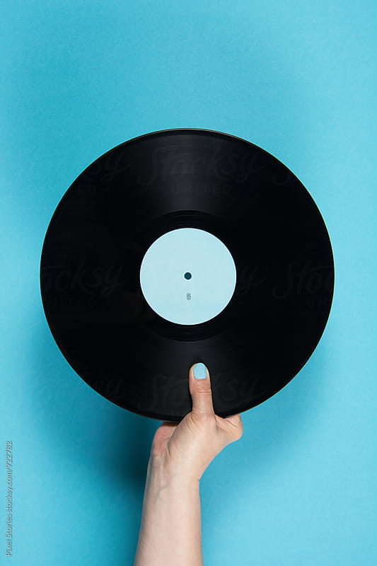 Hand holding vinyl record over blue background by Pixel Stories for Stocksy United