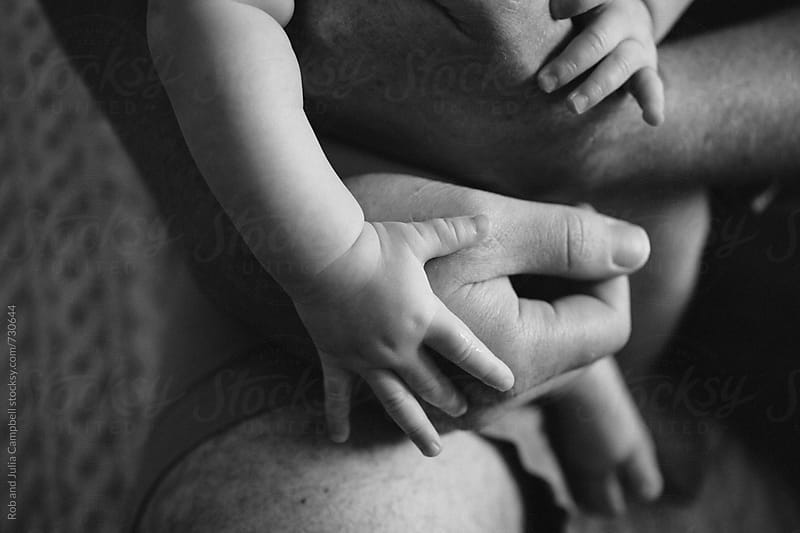 Close up of mans hands holding little baby by Rob and Julia Campbell for Stocksy United