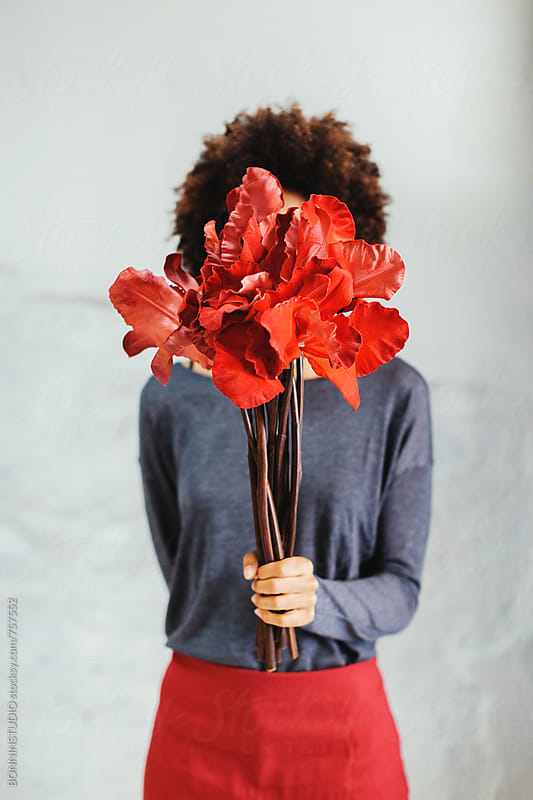 Woman covering her face with a bouquet of red flowers. by BONNINSTUDIO for Stocksy United