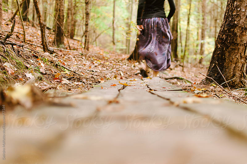 girl in long skirt running through autumn woods by Deirdre Malfatto for Stocksy United