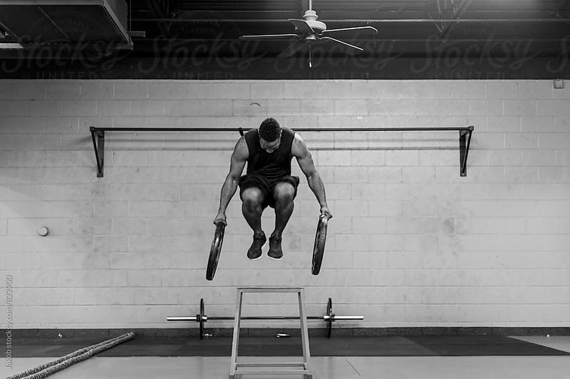 Fit and muscular african american athlete jumping with heavy weights in his hands by Jakob for Stocksy United