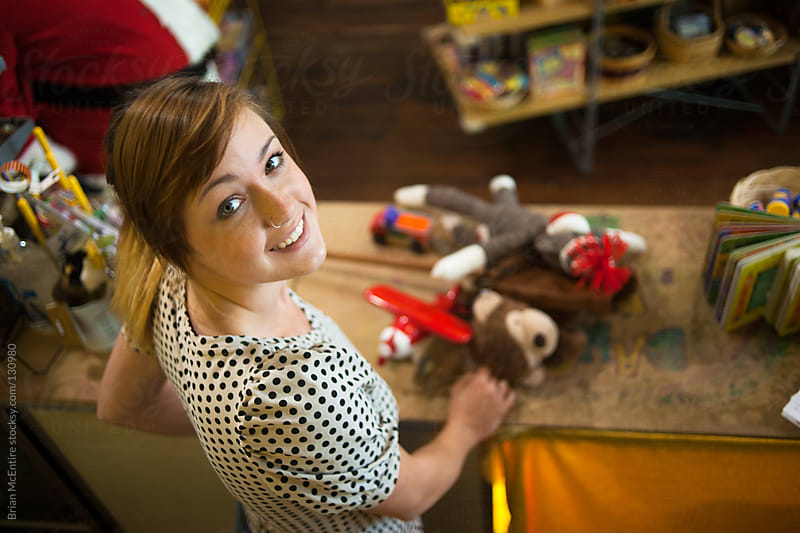 Cashier Woman Behind Toy Store Counter Looks Up At Viewer From I by Brian McEntire for Stocksy United