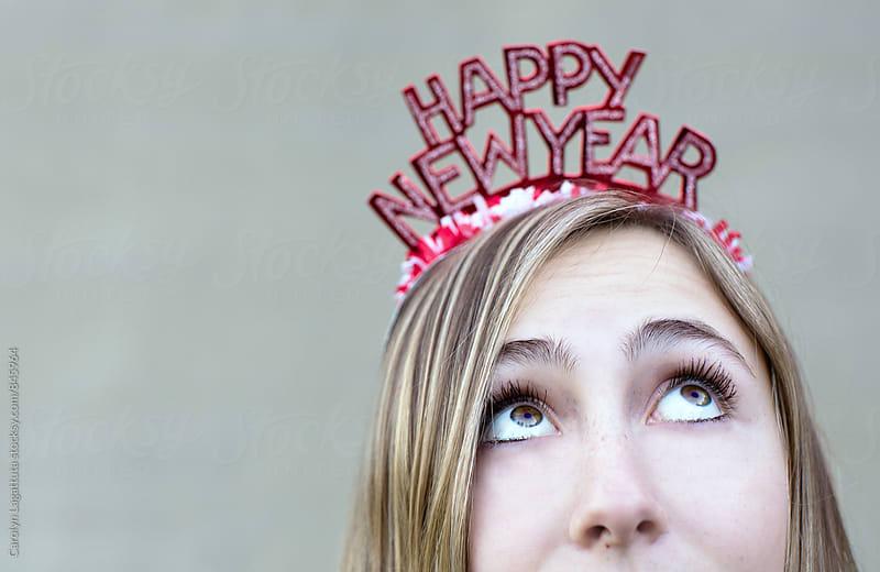 Female in a Happy New Year headband looking upward by Carolyn Lagattuta for Stocksy United