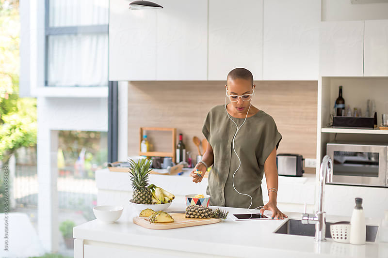 Young african American woman standing in kitchen by Jovo Jovanovic for Stocksy United