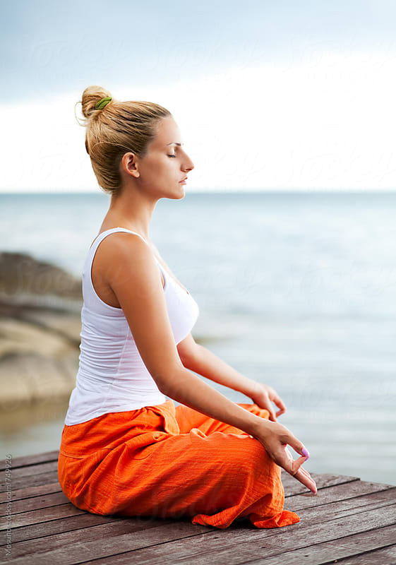 Young Woman Meditating by the Sea by Mosuno for Stocksy United