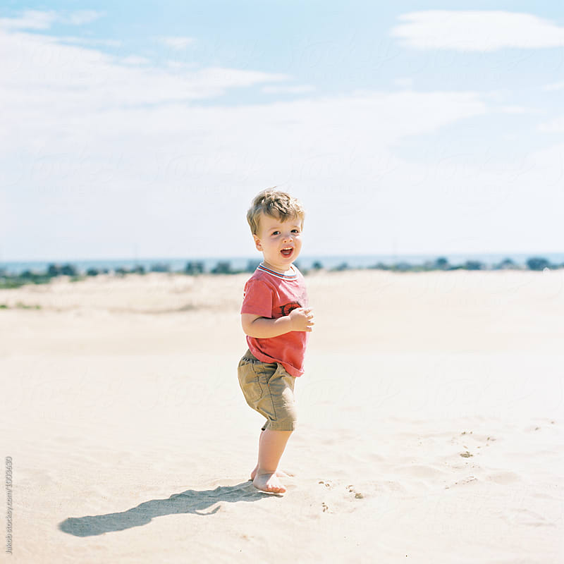 Cute young boy looking playful on a sand dune by Jakob for Stocksy United
