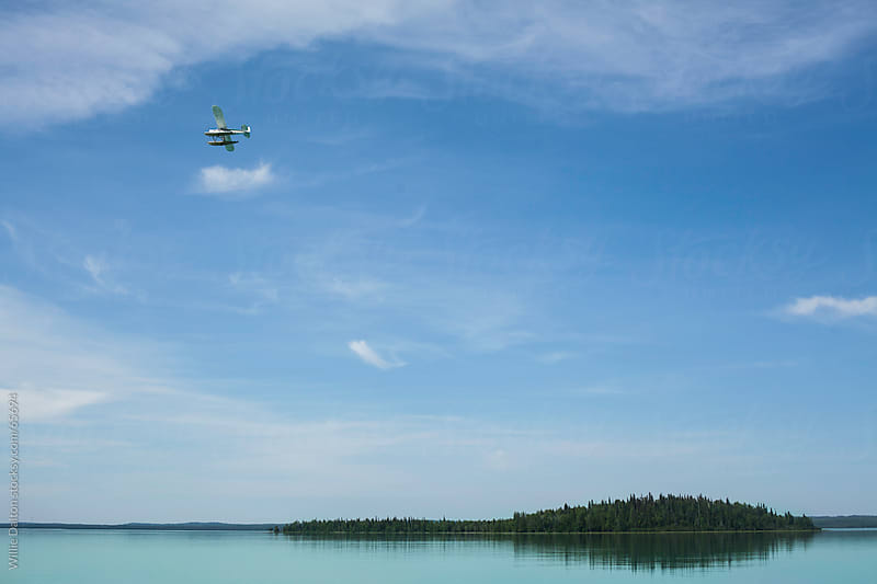 Sea Plane Flies Over a Calm Turquoise Lake by Willie Dalton for Stocksy United