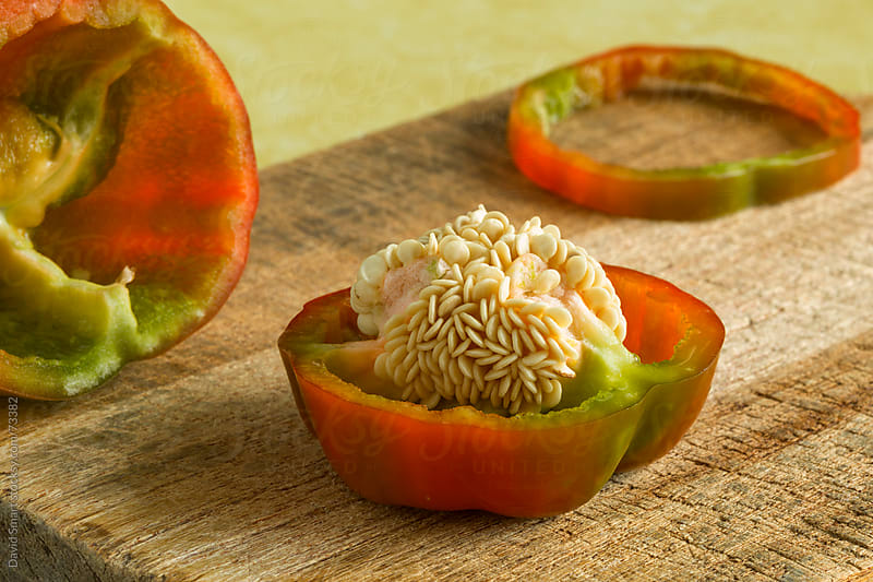 Bell pepper on a cutting board with seeds exposed  by David Smart for Stocksy United