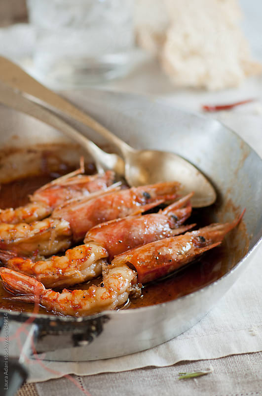 prawns in a pan cooked with honey and rosemary by Laura Adani for Stocksy United