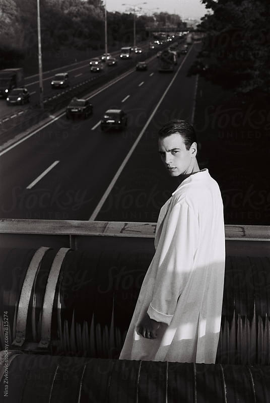 A young man walking over the highway. by Nina Zivkovic for Stocksy United