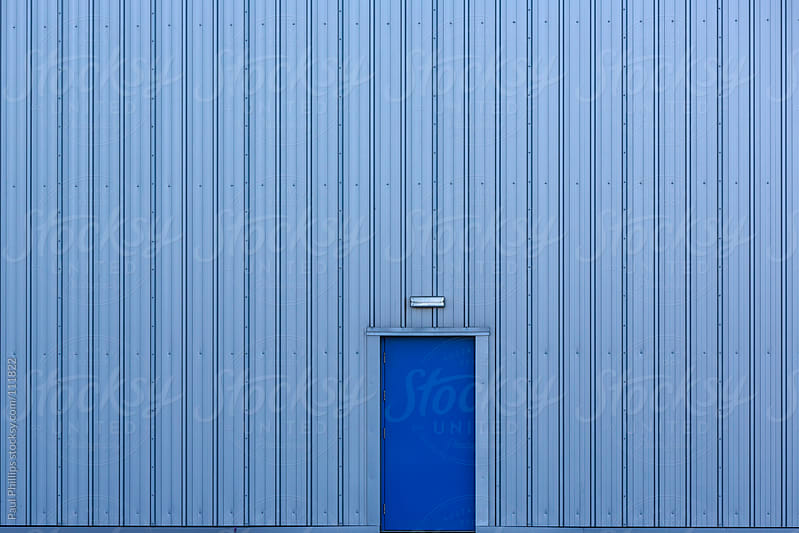 Blue door entry into a blue industrial building by Paul Phillips for Stocksy United