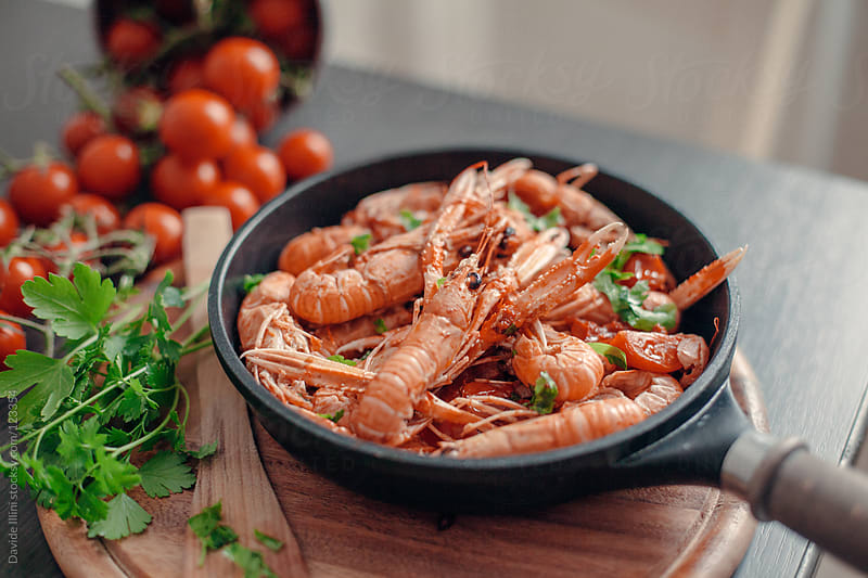 Scampi with tomatoes and parsley by Davide Illini for Stocksy United