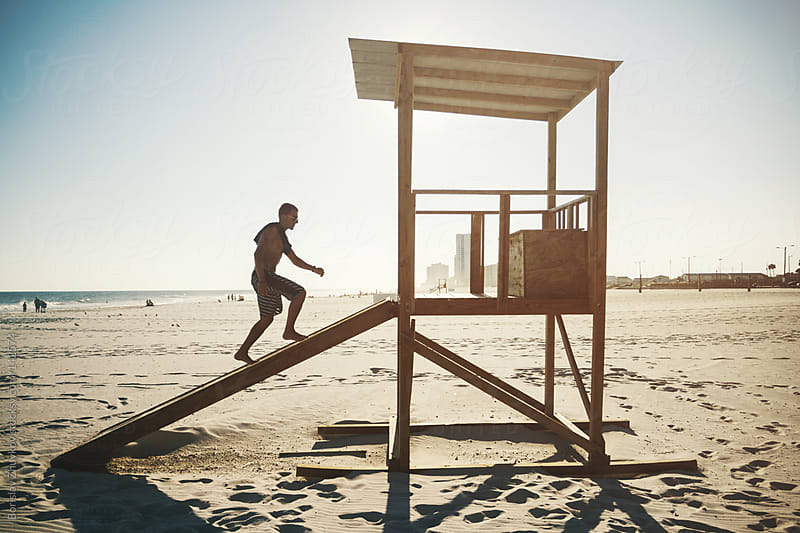 Young man is climbing to the lifeguard post  by Borislav Zhuykov for Stocksy United