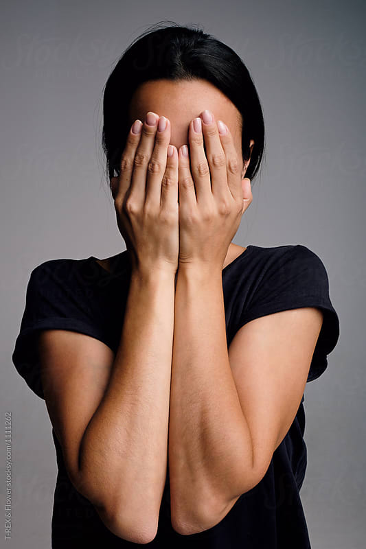Black-haired woman covering her face with hands
