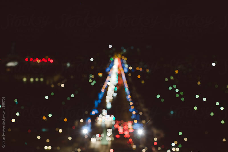 The lights of the Champs-Élysées and Arc de Triomphe, seen at night by Kathryn Swayze for Stocksy United