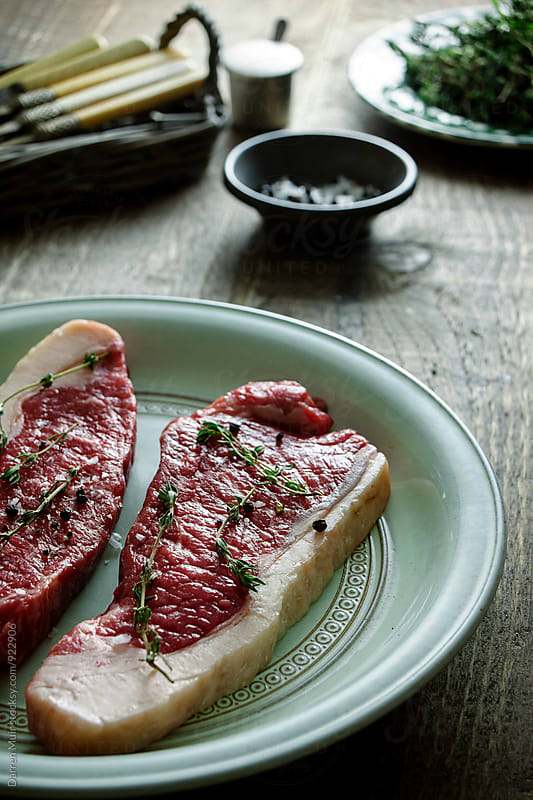 Sirloin steaks on a plate with seasoning. by Darren Muir for Stocksy United