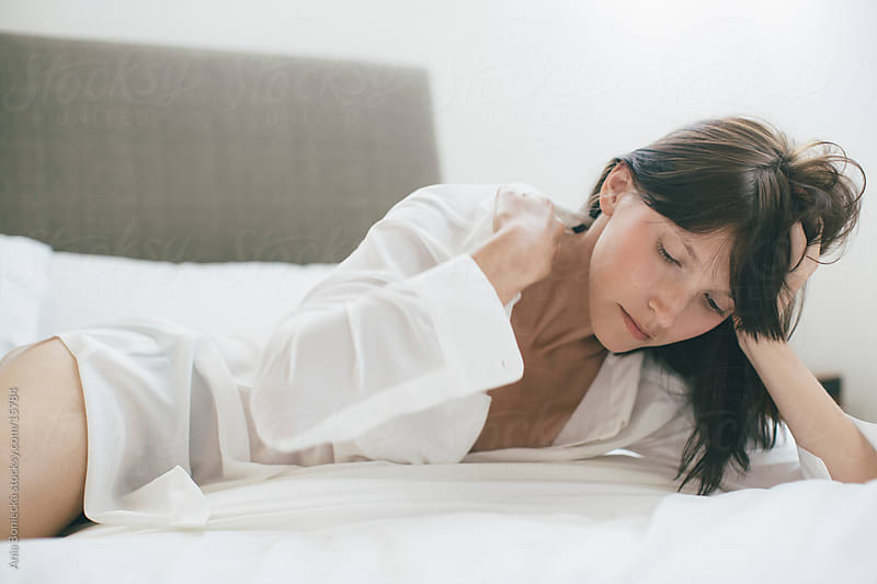 A beautiful woman lying in bed adjusting her collar by Ania Boniecka for Stocksy United