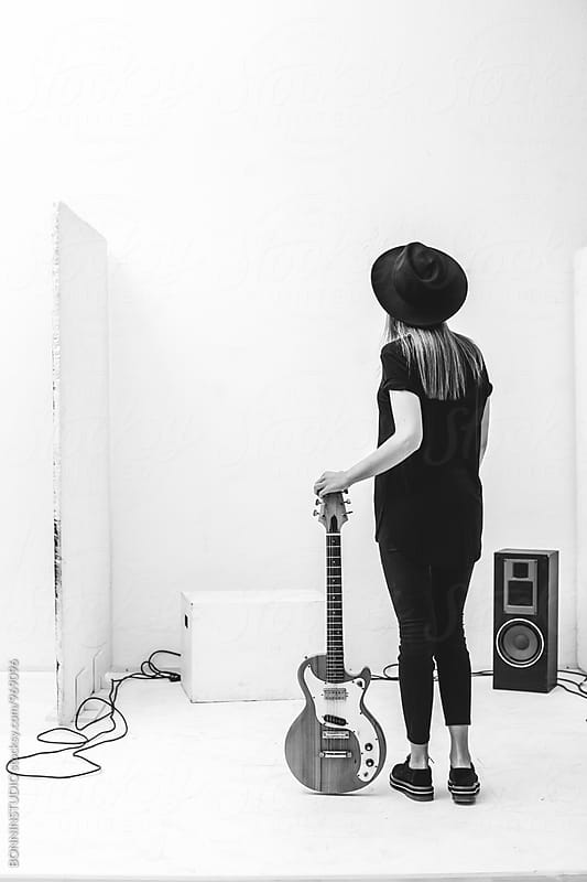 Back view of a rocker with her guitar in a recording studio. by BONNINSTUDIO for Stocksy United