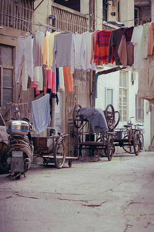 Laundry hangs over the back ally street in Shanghai, China by Shelly Perry for Stocksy United