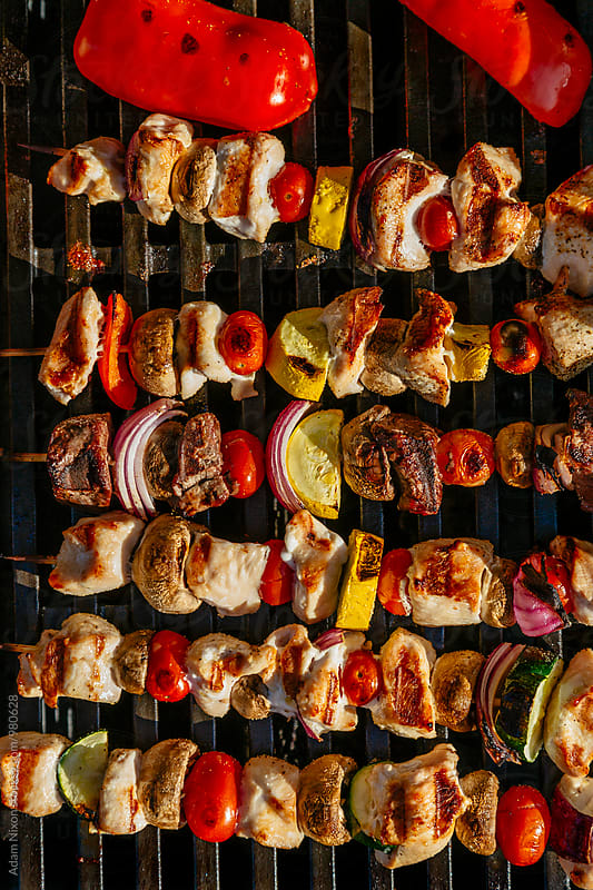 Chicken, steak and vegetable skewers on a grill by Adam Nixon for Stocksy United