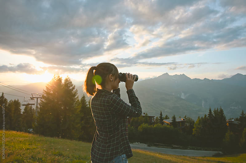 Woman with binoculars on a beautiful sunset in les Alps, France. by BONNINSTUDIO for Stocksy United