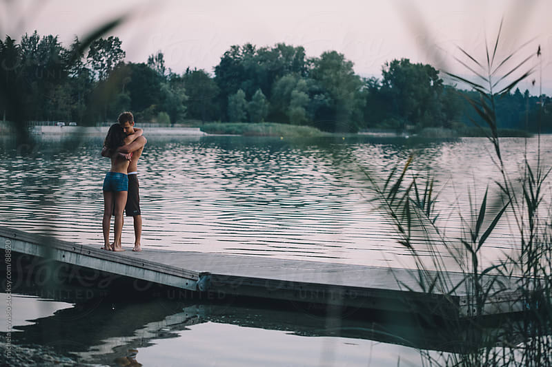 Couple embracing on a pier by michela ravasio for Stocksy United