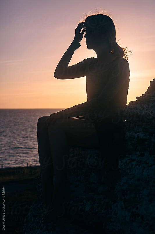 Silhouette of a woman by the sea at sunset by Lior + Lone for Stocksy United