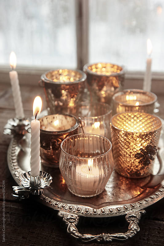 Closeup of silver votive candles in front of window by Sandra Cunningham for Stocksy United