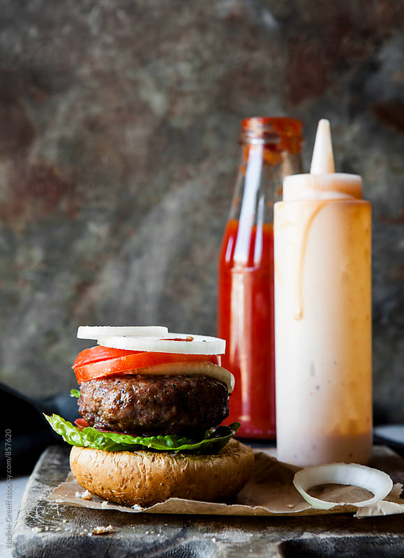 Juicy burger with tomato, onion and ketchup mayo sauce  by Nadine Greeff for Stocksy United