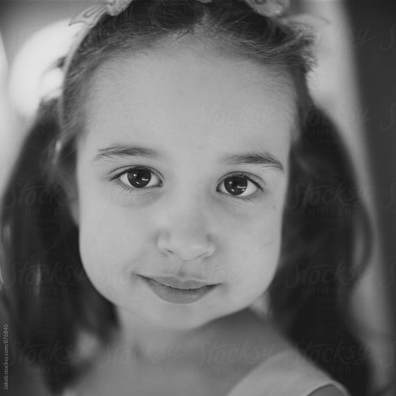 Black and white close up portrait of a beautiful young girl with big cheeks by Jakob for Stocksy United