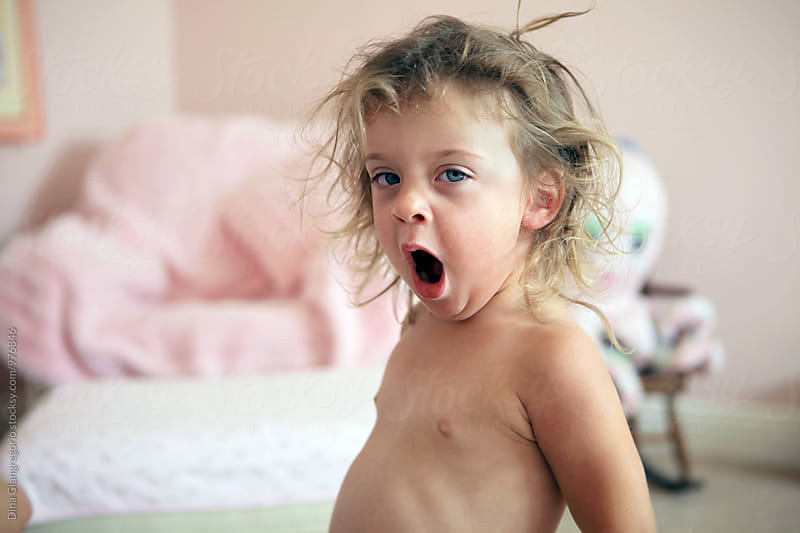 Yawning Toddler With Bed Head From Nap by Dina Giangregorio for Stocksy United