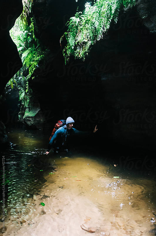 Male canyoner wading through a dark pool in a canyon. by Thomas Pickard Photography Ltd. for Stocksy United