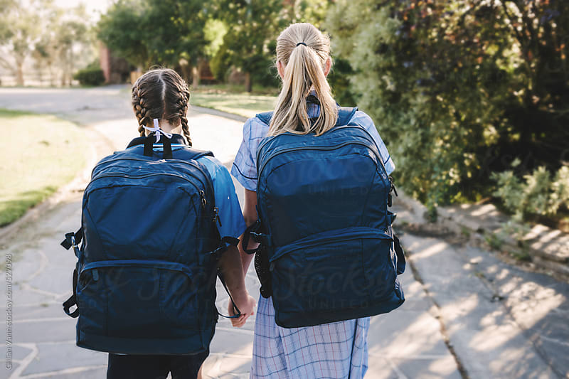 rear view of two girls in school uniform with large, navy backpacks by Gillian Vann for Stocksy United