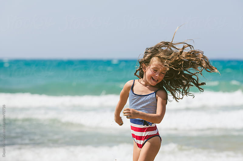 Little girl playing with the wind by Dejan Ristovski for Stocksy United