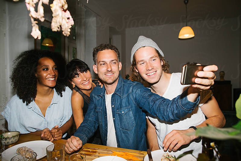 Snapshot of Four Mixed Race Friends Taking Selfie at Informal Dinner Party by Julien L. Balmer for Stocksy United