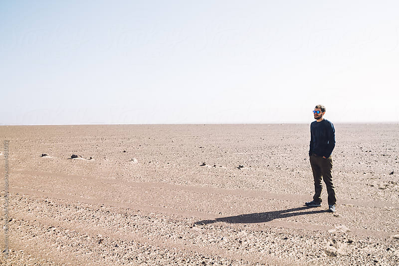 Young man in the middle of nowhere in desert landscape by Alejandro Moreno de Carlos for Stocksy United
