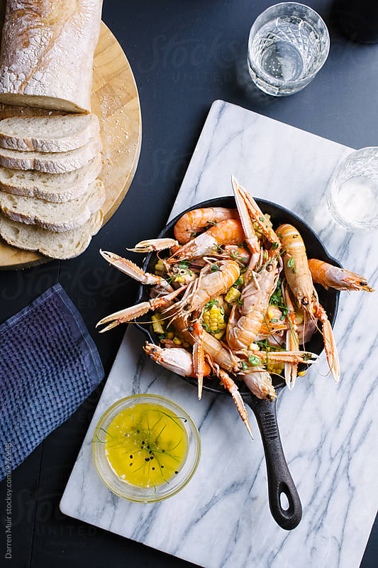 Shrimp and langoustines, served with bread and garlic butter. by Darren Muir for Stocksy United