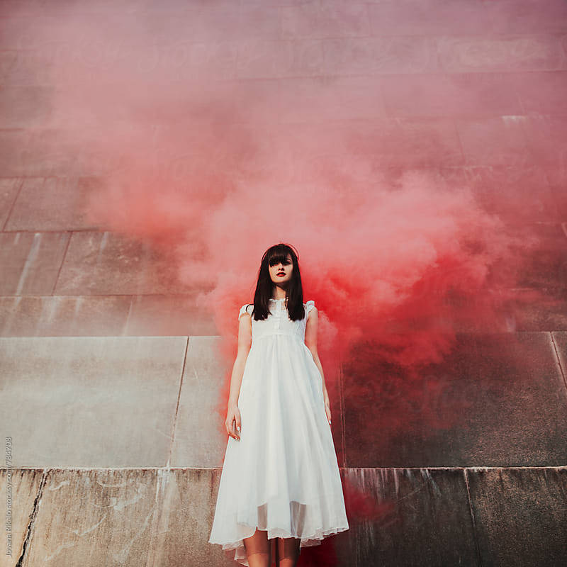 Portrait of a young woman wearing white dress and smoke behind her by Jovana Rikalo for Stocksy United