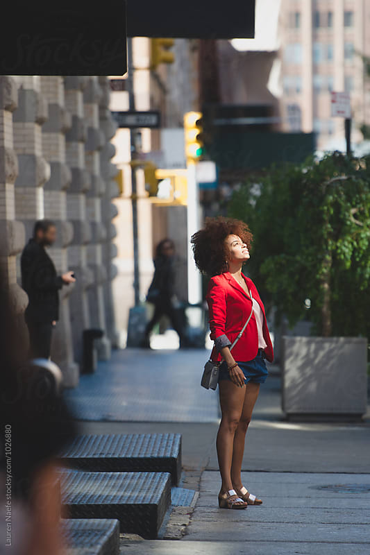 Young woman standing in the street in New York City by Lauren Naefe for Stocksy United